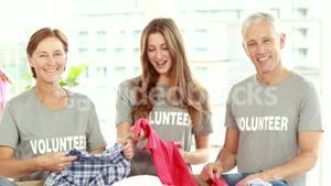 Smiling friends volunteers separating clothes