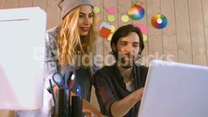 Smiling casual designers working over a laptop