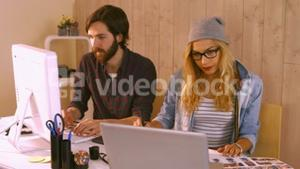 Casual designers working on laptop and graphic tablet