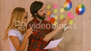 Casual designers working on a post its wall