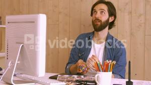 Hipster worker throwing ball at desk