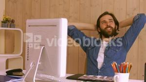 Hipster worker relaxing at desk
