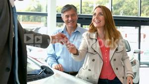 Couple taking keys from businessman