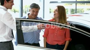 Customers checking out their new car