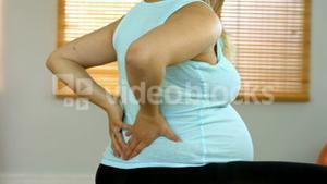 Pregnant woman rubbing her lower back