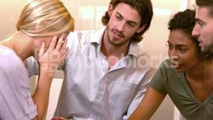 Stressed out woman being comforted by coworkers