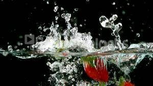Strawberries falling in water on black background