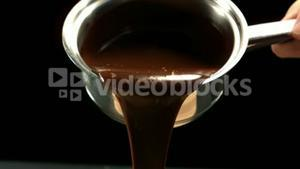 Saucepan pouring out melted chocolate