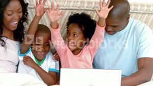 Happy family shopping online with laptop