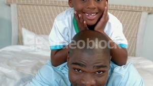 Father and son posing on bed