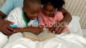 Father and children reading in bed