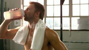Fit man drinking protein shake in gym