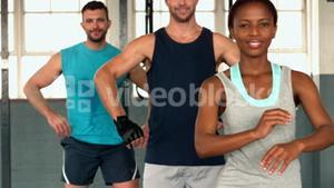 Fit people posing at camera in gym