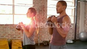 Fit couple lifting kettlebells together