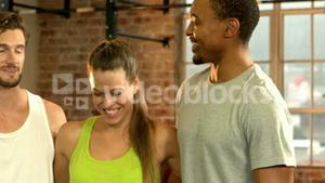 Fit people smiling together in crossfit gym