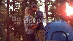 Couple hugging beside their tent