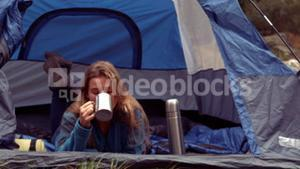 Woman enjoying hot drink in her tent