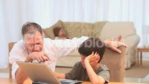 Grandfather helping his grandson using a laptop