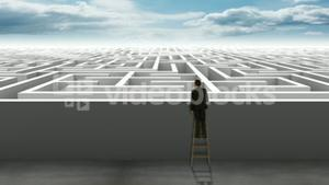 Businessman on ladder looking at maze