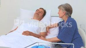 Elderly woman paying her sick husband a visit