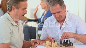 Elderly friends playing chess