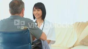 A patient in wheelchair talking with his nurse