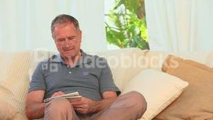 Retired man sitting on a sofa with a newspaper