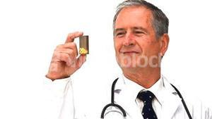 Elderly doctor holding yellow pills