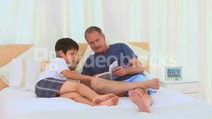 Little boy reading a book with his grandfather