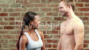Fit couple talking in crossfit gym
