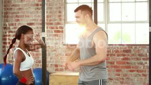 Fit couple high fiving in crossfit gym