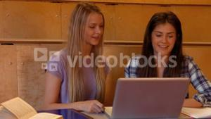Two students in class with a laptop