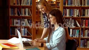 Two students working on a laptop