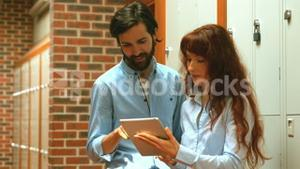 Two happy students using a tablet