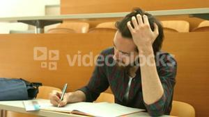 Stressed student taking down notes