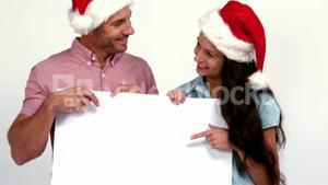 Casual festive couple pointing to card