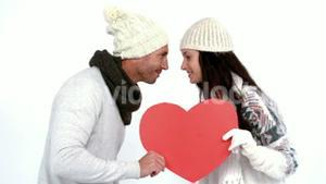 Winter couple holding heart card