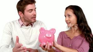 Poor couple with moving box and piggy bank