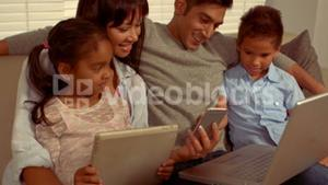 Smiling Hispanic family on different devices