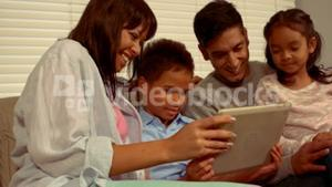Smiling Hispanic family on a tablet