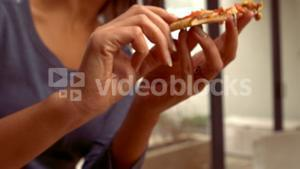 Smiling Hispanic woman eating pizza
