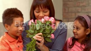 Smiling Hispanic mother has received flowers from her children