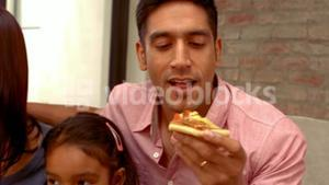 Smiling Hispanic family eating pizza in living room