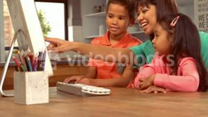 Smiling Hispanic mother on computer with her children