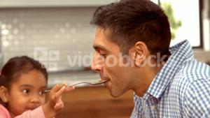 Smiling Hispanic father is fed by his daughter
