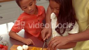 Smiling Hispanic father is cooking with his children