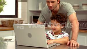 Smiling Hispanic father on computer with his son