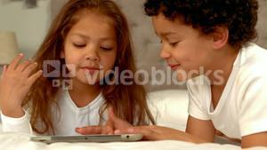 Hispanic children playing together on a tablet