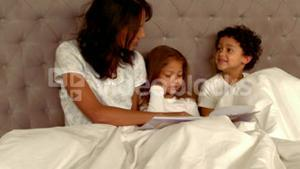 Smiling Hispanic mother with her children in bed