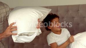 Smiling Hispanic family doing a pillow fight